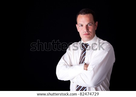 Portrait of a  business man, arms crossed, isolated on black background. Studio shot. - stock photo