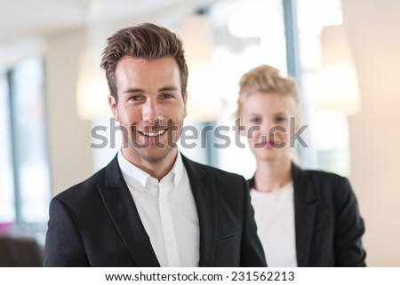 portrait of a business team at office looking at camera, man at foreground and a woman at the background - stock photo