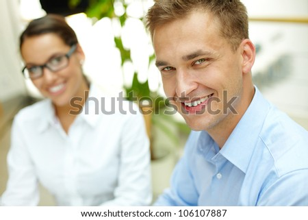 Portrait of a business team, guy being in the front, girl sitting behind him - stock photo