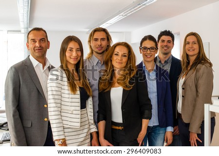 Portrait of a business team inside the office, all rather young - might be a startup company - stock photo