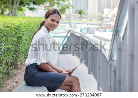 Portrait of a business woman. African businesswoman businessman standing near a fountain in downtown Dubai among the skyscrapers and holding tablet in hand and smiling directly at the camera - stock photo