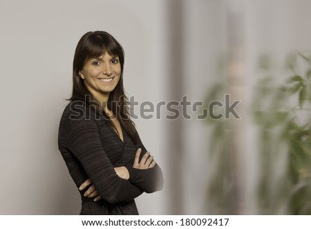 Portrait of a business woman, in her mid 30's, standing in an office, smiling. / smiling modern business woman - stock photo