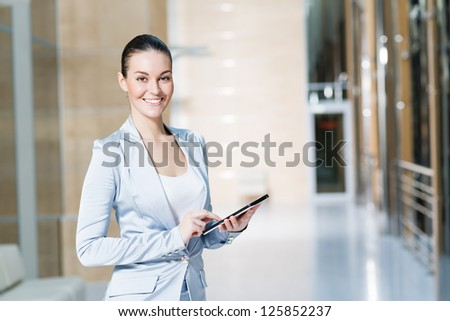Portrait of a business woman in the tablet at the office, turned around and looking at the camera - stock photo