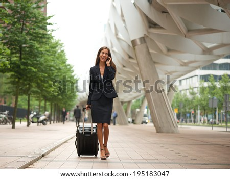 Portrait of a business woman on mobile phone in the city - stock photo