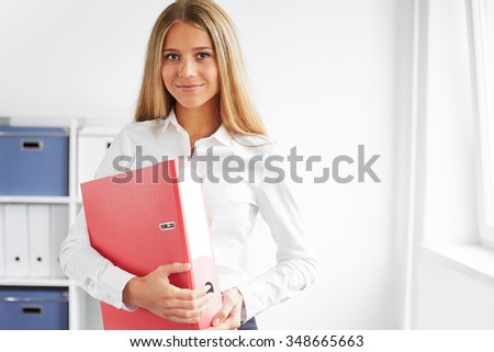 Portrait of a business woman standing in office with folder - stock photo