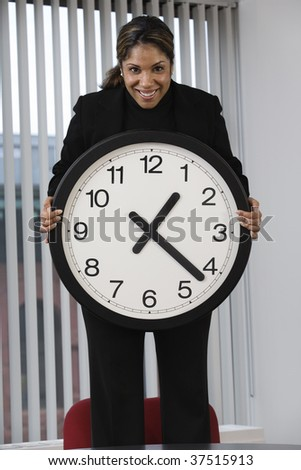 Portrait of a business woman standing on an office chair in a meeting and showing the deadline using a wall clock for emphasis. - stock photo