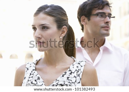 Portrait of a businessman and a businesswoman standing in the city and looking in different directions. - stock photo