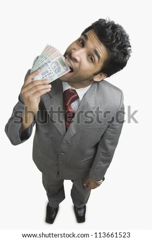 Portrait of a businessman biting Indian currency notes - stock photo