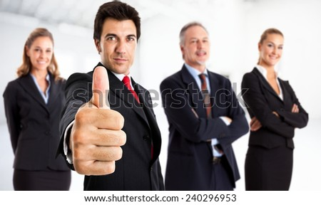 Portrait of a businessman giving thumbs up in front of his team - stock photo