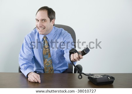 Portrait of a businessman holding a telephone handset and smiling - stock photo