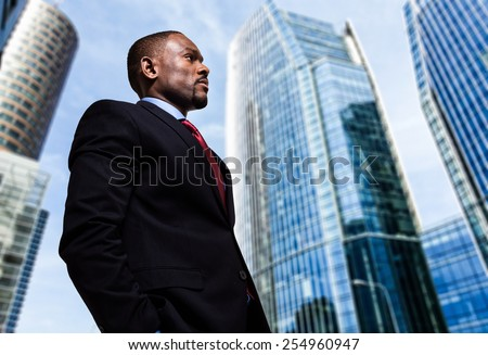 Portrait of a businessman in front of skyscrapers - stock photo