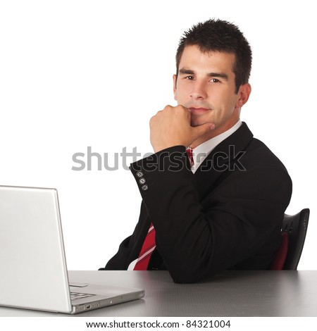 Portrait of a businessman looking into camera while sitting.Hand on chin - stock photo