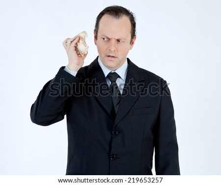 Portrait of a businessman, mature, bald, wearing a suit and tie, holding a seashell next to your ear, with scared face on white background - stock photo