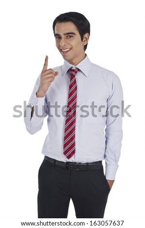 Portrait of a businessman pointing and smiling - stock photo