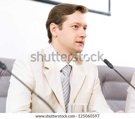 Portrait of a businessman, said into the microphone, the meeting - stock photo