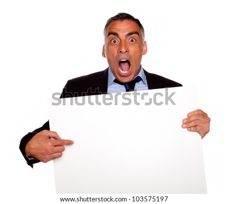Portrait of a businessman screaming, pointing and holding a white card with copyspace on isolated background - stock photo