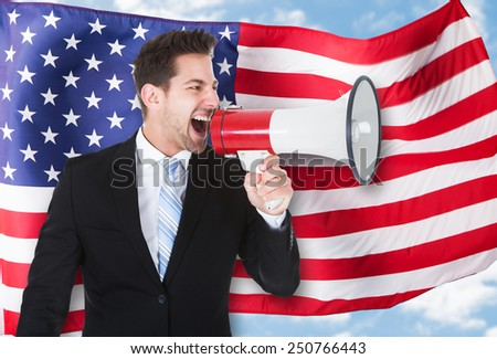 Portrait Of A Businessman Shouting Through Megaphone In Front Of American Flag - stock photo