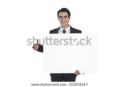 Portrait of a businessman showing a blank placard and smiling - stock photo