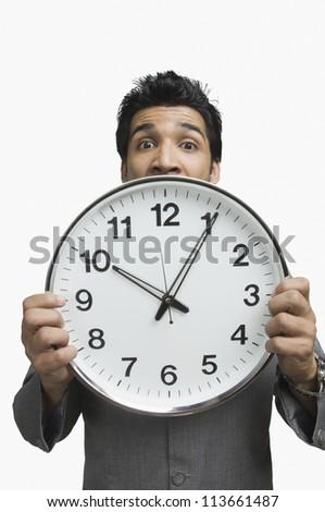 Portrait of a businessman showing a clock - stock photo