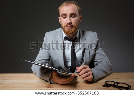 Portrait of a businessman sitting at the table with clipboard over dark background - stock photo