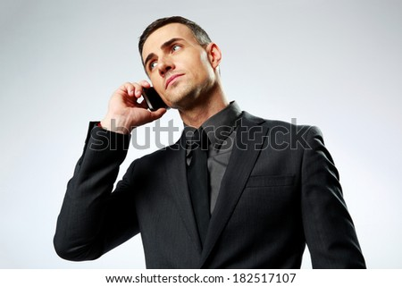 Portrait of a businessman speaking on cell phone isolated on a white background - stock photo