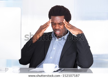 Portrait Of A Businessman Suffering From Headache In Office - stock photo