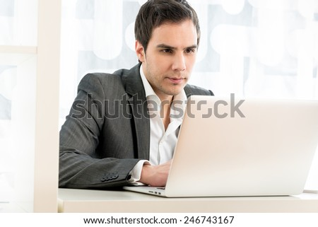 Portrait of a businessman typing on a white laptop computer keyboard, low angle view from the back of the computer. - stock photo