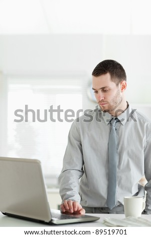 Portrait of a businessman using a laptop in his kitchen - stock photo