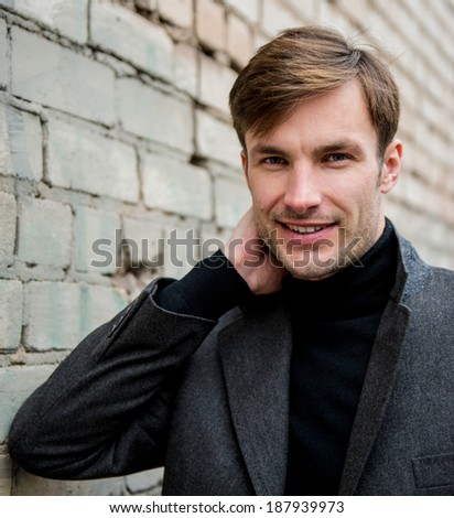 Portrait of a businessman who is smiling and looking away against a brick wall, closeup  - stock photo
