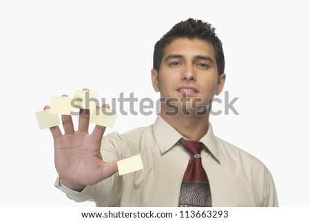 Portrait of a businessman with adhesive notes on his fingers - stock photo