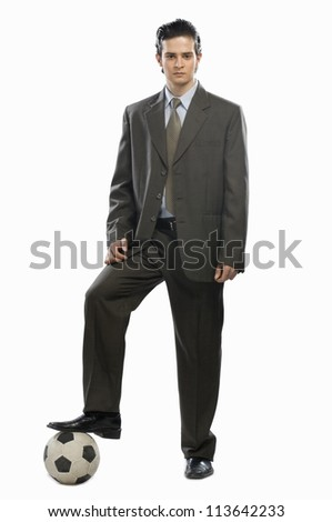 Portrait of a businessman with his foot on a soccer ball - stock photo
