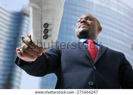 Portrait of a businessmen shaking hands in a business environment - stock photo