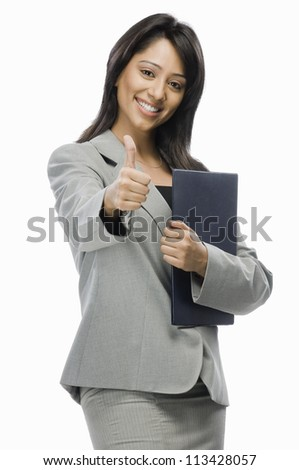 Portrait of a businesswoman holding files and showing thumbs up - stock photo
