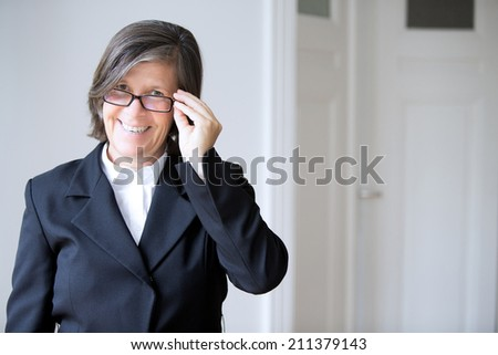 Portrait of a businesswoman holding her glasses and smiling - stock photo