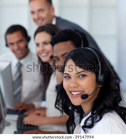 Portrait of a businesswoman in a call center with her multi-ethnic team - stock photo