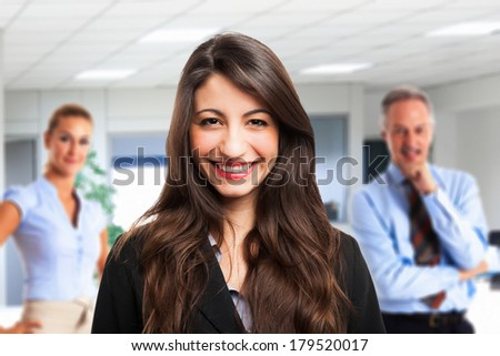 Portrait of a businesswoman in front of his team - stock photo