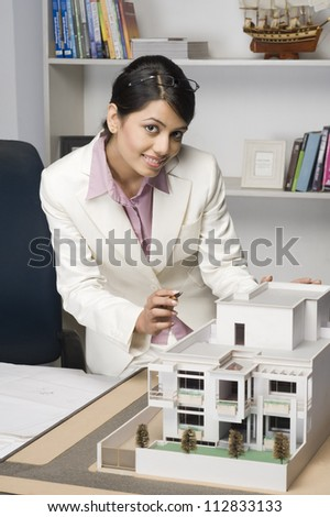 Portrait of a businesswoman near a model home in an office - stock photo