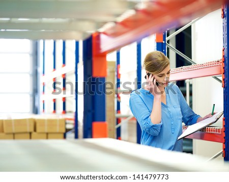 Portrait of a businesswoman on the phone and checking inventory in warehouse - stock photo