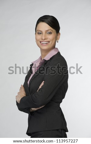 Portrait of a businesswoman smiling with arms crossed - stock photo