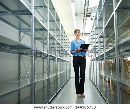 Portrait of a businesswoman standing in warehouse with clipboard next to metallic shelves and racks - stock photo