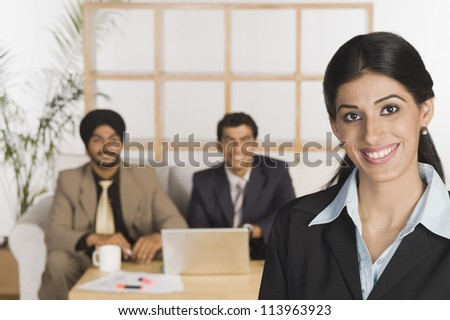 Portrait of a businesswoman with her colleagues in the background - stock photo