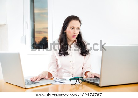 Portrait of a businesswoman with lots of paperwork at office desk - stock photo