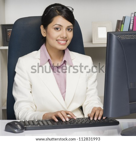 Portrait of a businesswoman working on a desktop PC in an office - stock photo