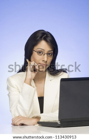 Portrait of a businesswoman working on a laptop - stock photo