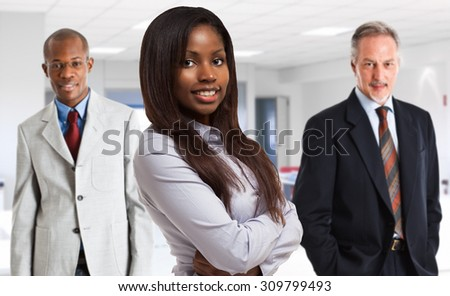 Portrait of a businesswon in front of her team - stock photo