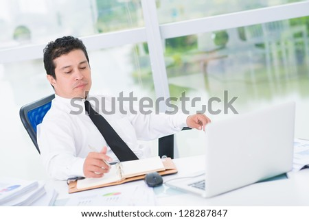 Portrait of a busy businessman in the office - stock photo