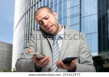 Portrait of a busy businessman using three phones at once - stock photo