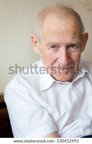 portrait of a calm senior man in white shirt - stock photo