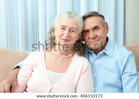 Portrait of a candid senior couple enjoying their retirement. Affectionate elderly couple with beautiful beaming friendly smiles posing together in a close embrace in their living room - stock photo