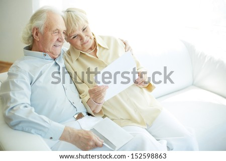 Portrait of a candid senior couple sitting and reading letter - stock photo